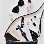 Handtasche mit Sonnenbrille Lippenstift und anderen weiblichen Utensilien