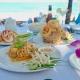 Tisch am Meer mit feinen Speisen - eurolanguage Fachübersetzungen