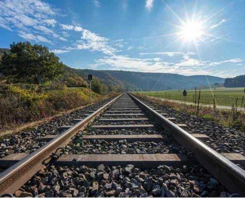 Eisenbahnschiene, Landschaft und Sonne - Übersetzungen